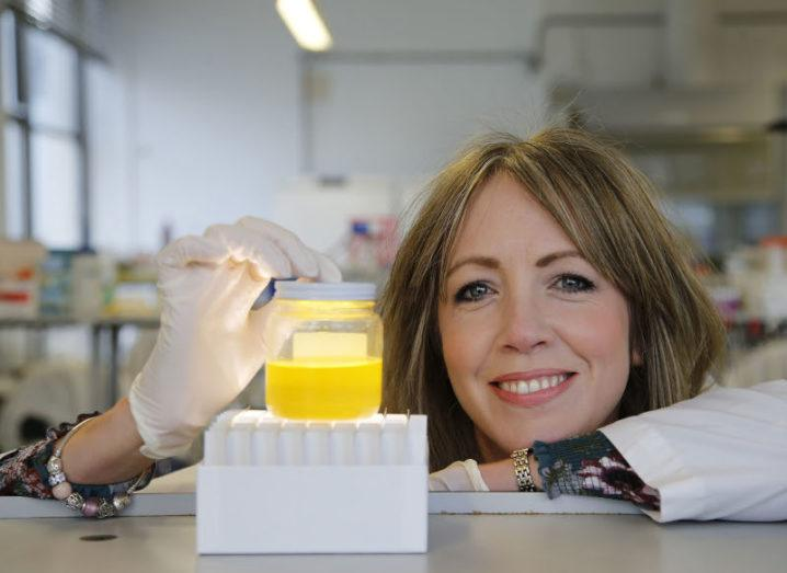 Dr Antoinette Perry from Epicapture poses with a urine sample. She is in a lab wearing gloves and a lab coat.