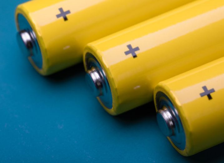 A close-up of the tops of three yellow batteries against a dark blue background.