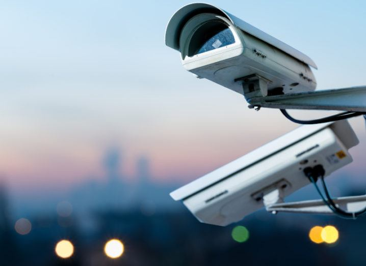 Two white CCTV cameras pointed in opposite directions against the backdrop of an out-of-focus cityscape.