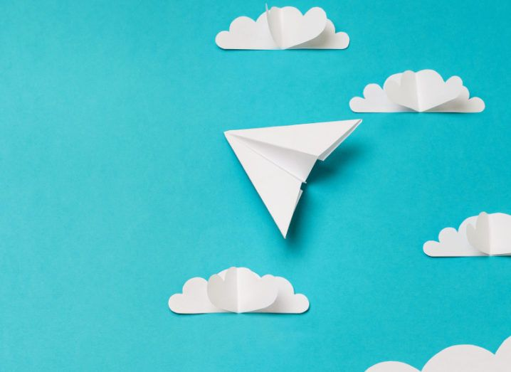 Several paper cut-outs of clouds and a paper aeroplane pointing upwards sit on a turquoise background.