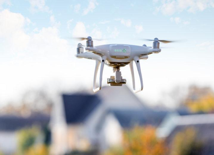 A white drone mid-flight. In the background is an out-of-focus suburban area with a number of houses on a sunny day.