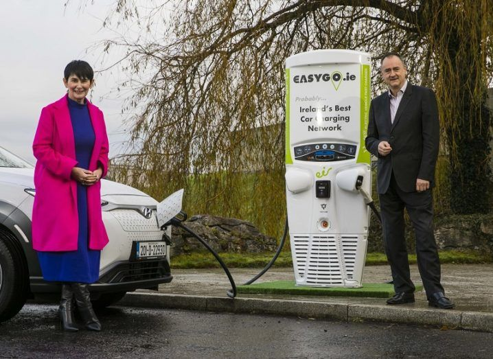 Carolan Lennon in a pink coat and Gerry Cash in a black suit standing beside an EV and charging point.