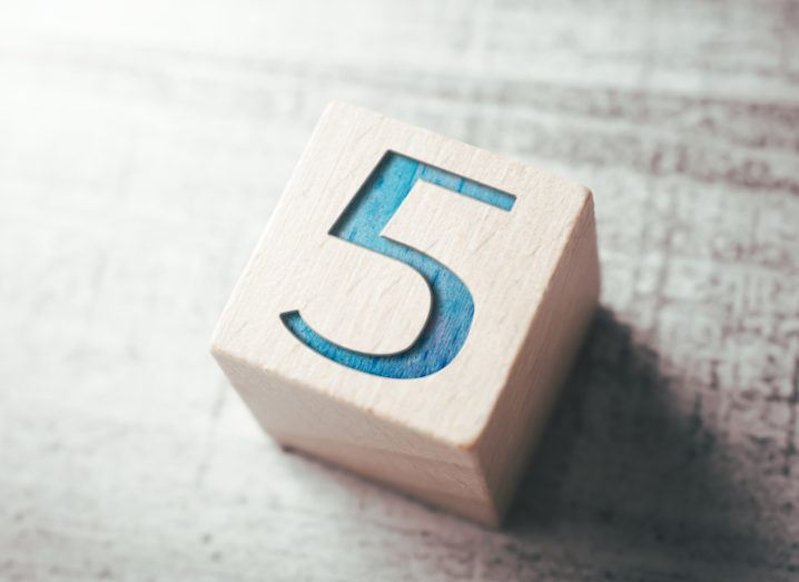 A light-coloured wooden block resting on a grey surface with a blue number five carved into the top of it.