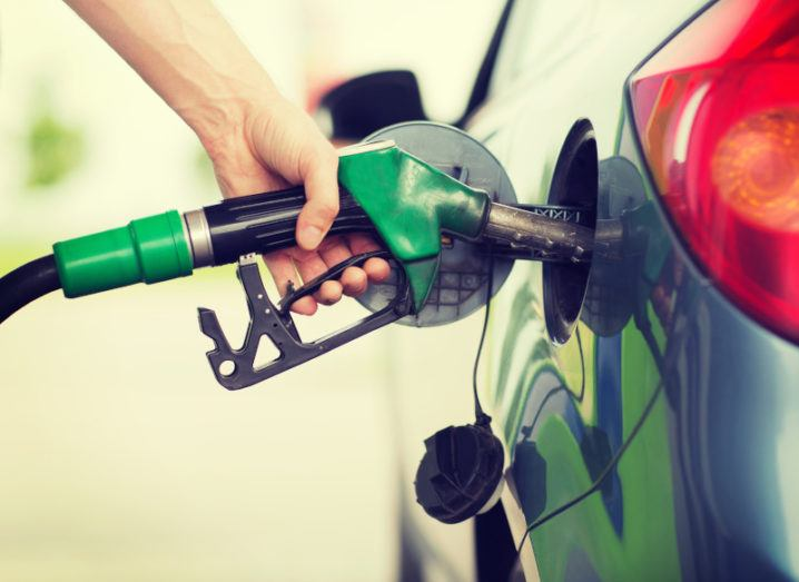 A hand clasped around a green fuel pump, which is inserted into the tank of a blue car.