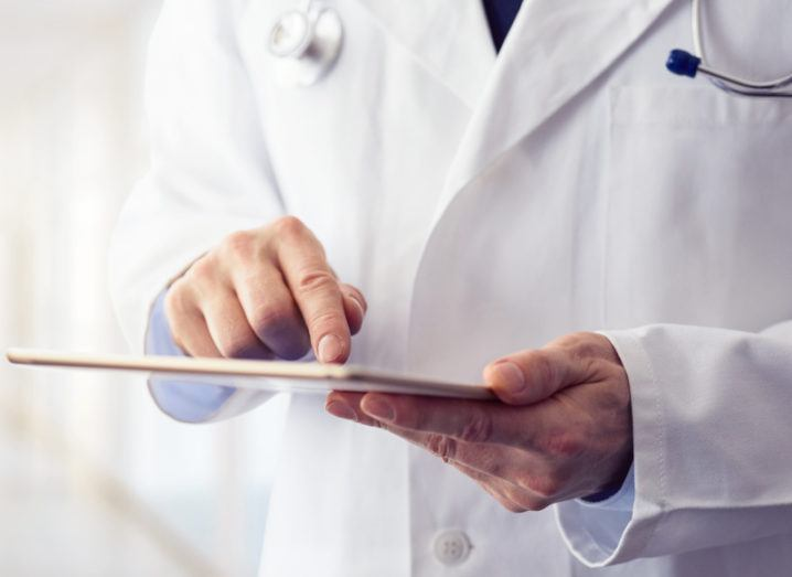 A close up of a doctor's hands holding a tablet, inputting data. He's wearing a lab coat and standing in a hallway.
