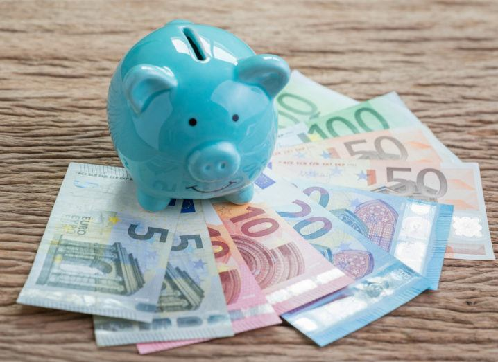 A light blue piggy bank sits on a wooden table with a variety of euro bank notes fanned out in front of it.