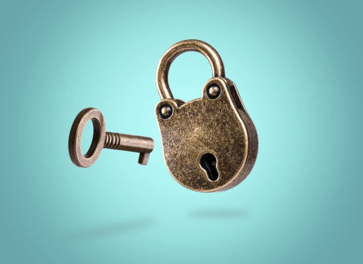 An old, bronze, rounded padlock and a matching key float beside each other against a bright turquoise background.