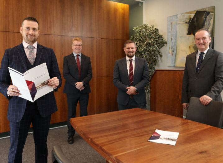 Four men in suits from Tekenable and Baker Tilly are standing in a wood-panelled boardroom and smiling into the camera.