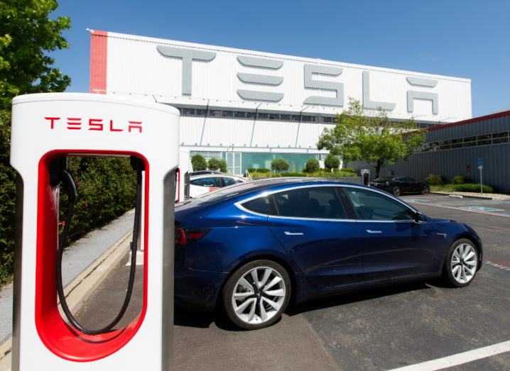 A dark blue car is parked beside a Tesla charging station. In the distance, a large white building with the Tesla logo looms over trees.