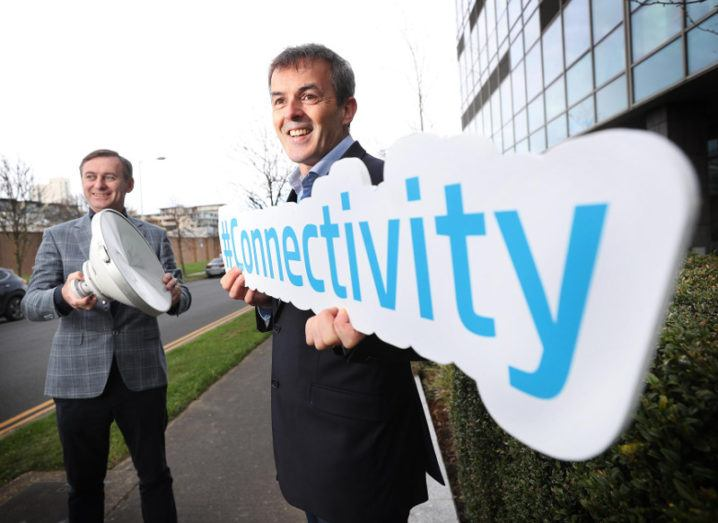 Two men in suits are standing outdoors and smiling at something off camera while holding a sign that says connectivity at the Viatel Group and Irish Telecom acquisition announcement.