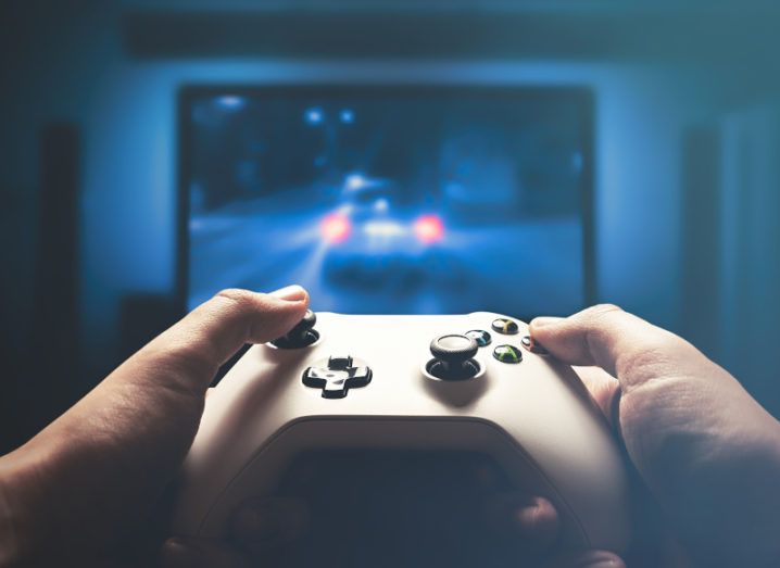 Hands holding a silver video game controller, pointing at a large television with a driving game on the screen.