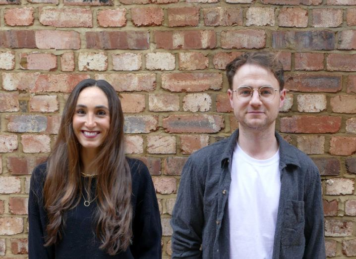 A casually dressed man and woman stand in front of a red brick wall.