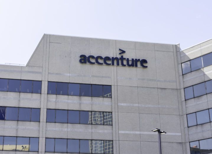 An upward angle of a high, grey office building with many windows against a blue sky. A black Accenture logo is on the top of the building.