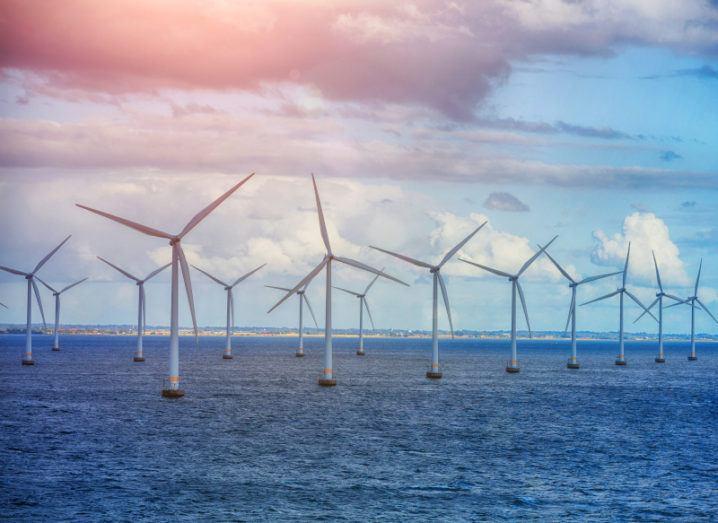 A row of wind turbines in the sea beneath a blue sky.