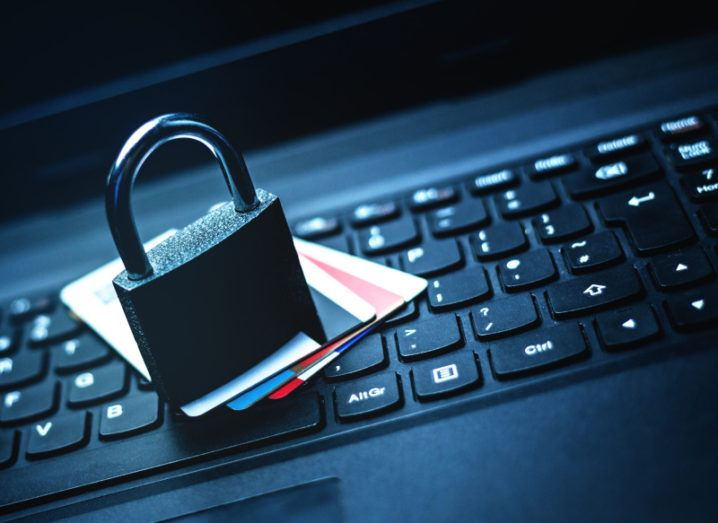 A padlock and a number of credit cards sit on top of a laptop keyboard.