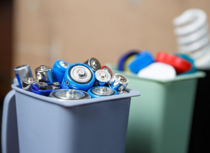 Miniature recycling bins are filled with batteries, plastic and bulbs.