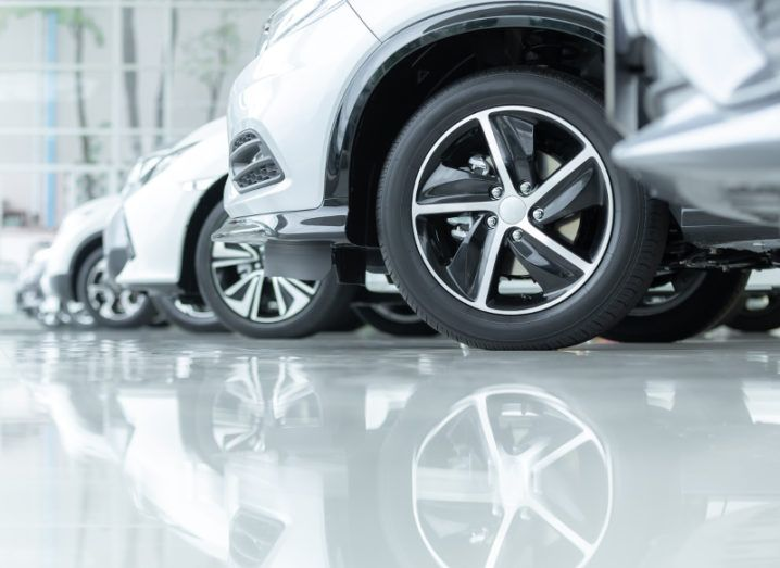 A fleet of silver cars reflecting off a white floor.