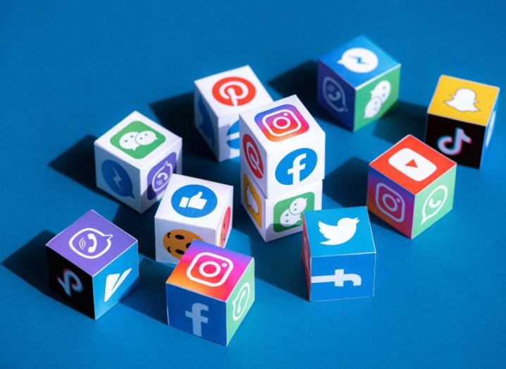 A collection of paper cubes printed with logos of social media platforms and messaging apps such as Facebook, Instagram, YouTube, Twitter and others.