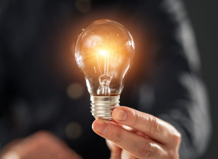 A person's hand holds up a bright lightbulb.
