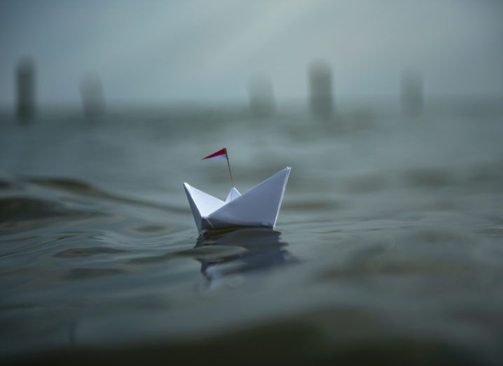 A paper boat floats on an uneasy body of water. The weather is dark and threatening.