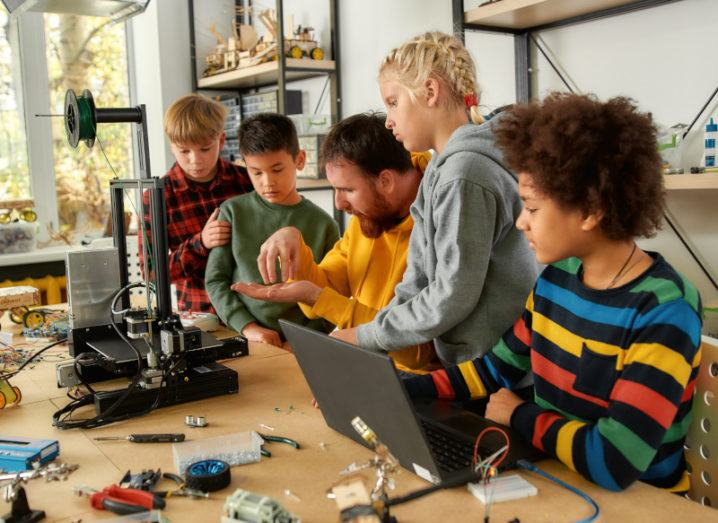 A group of children gather around an instructor in a workshop, who is showing them how to use a 3D printer.