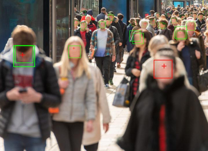 People walking down a busy high street. Their faces are blurred but overlaid with coloured frames, signifying facial recognition technology.