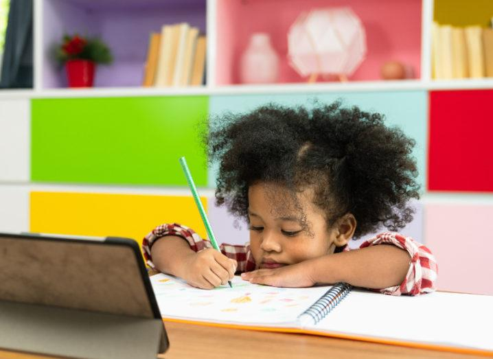 A young girl is doing schoolwork in front of colourful drawers at a desk with a tablet, representing remote learning.
