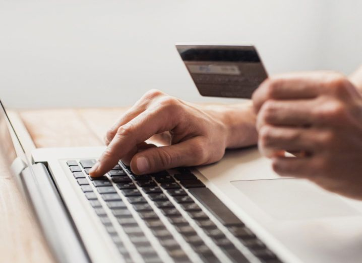 A hand is holding a payment card while working on a laptop.
