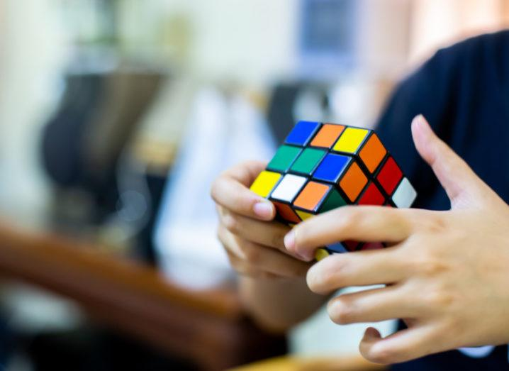 Close-up of a woman's hands as she is solving a Rubik's cube.