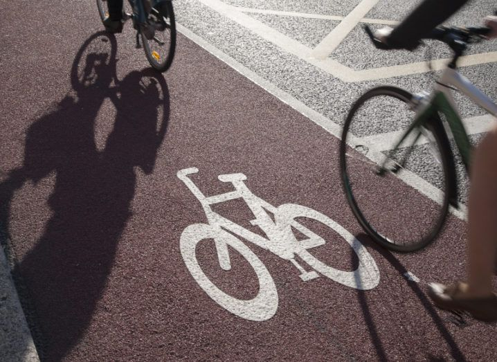 Two cyclists are going down a red cycle lane on the side of a Dublin road.