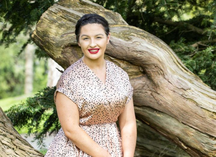SafeCare Nursing Solutions founder Ali-Rose Sisk sits outside up against a tree in a patterned dress.