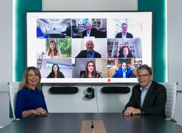Arkphire's Aisling Bolger and Paschal Naylor sit at a boardroom table facing the camera. Behind them, a large screen shows a video conference call with many other people.