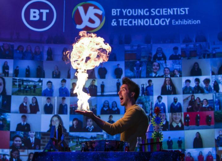 A man performing a fire trick stands in front of a large screen that says 'BT Young Scientist and Technology Exhibition' and features images of students taking part in the event.
