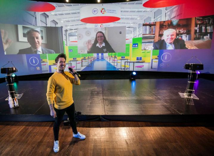 A man in a yellow jumper stands on a large stage at the BT Young Scientist and Technology Exhibition. Behind him is a large screen with three people on video links.