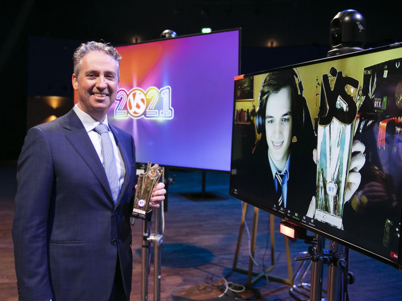 BT's Shay Walsh stands in a room at the Mansion House, presenting a gold award to Greg Tarr, who appears on a large screen beside him.