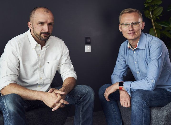 Two men, the founders of salon booking app Booksy, are sitting in a dark room.