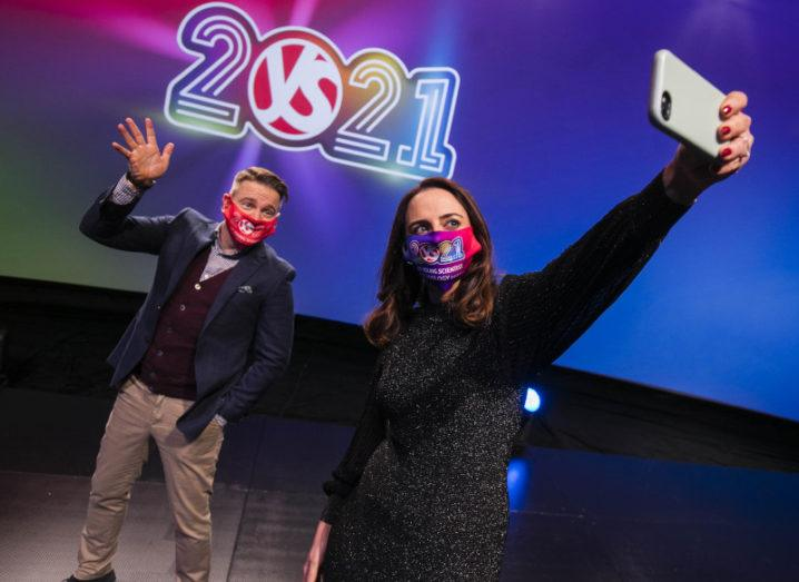 A man and woman wearing protective face masks stand in front of the BT Young Scientist 2021 logo taking a selfie.