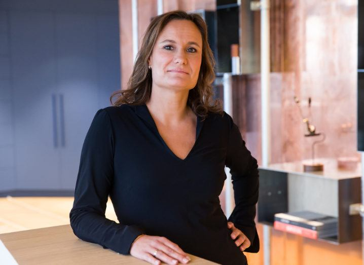 Gillian Tans, chair of Booking.com, stands in a brightly lit office and leans on a wooden table.