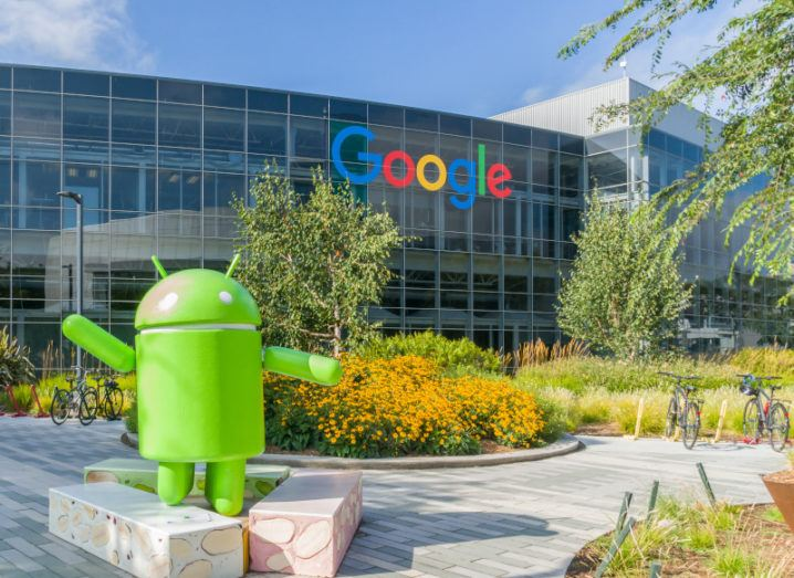 A large glass building with the colourful Google logo across the top. At the front of the building is a small statue of the green Android character.