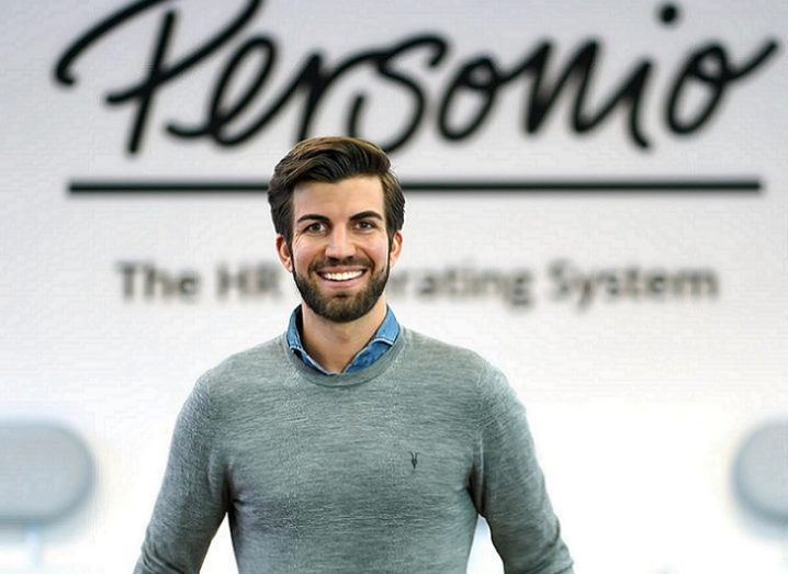 Chief executive of Personio Hanno Renner is standing in front of a wall that bears the company's name.