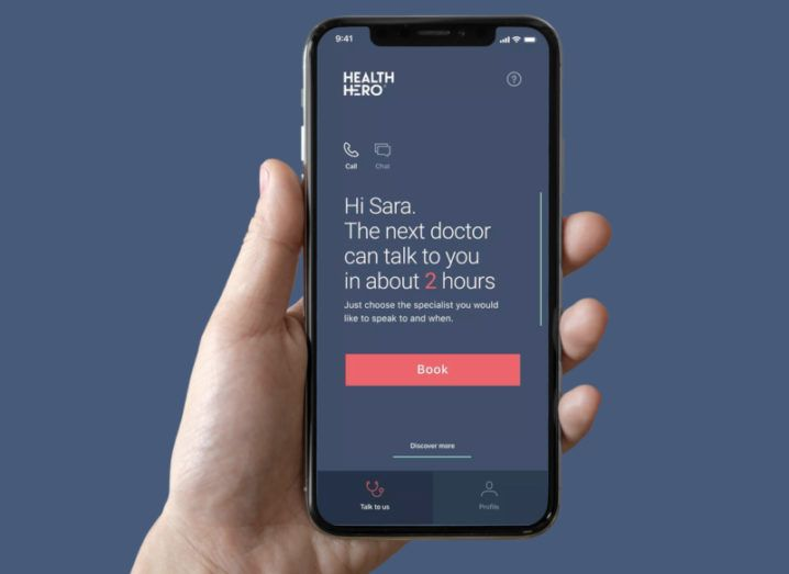A hand is holding a smartphone with the HealthHero app open on the screen. It is showing the option to book a doctor's appointment.