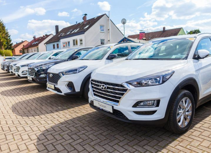 A line of Hyundai cars on a sunny day with houses in the background.