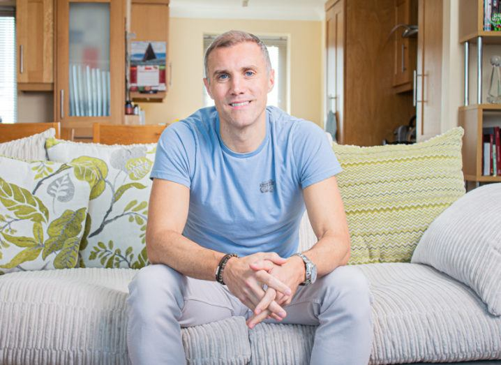 A man wearing light-coloured T-shirt and jeans sits comfortably on a couch in his home.