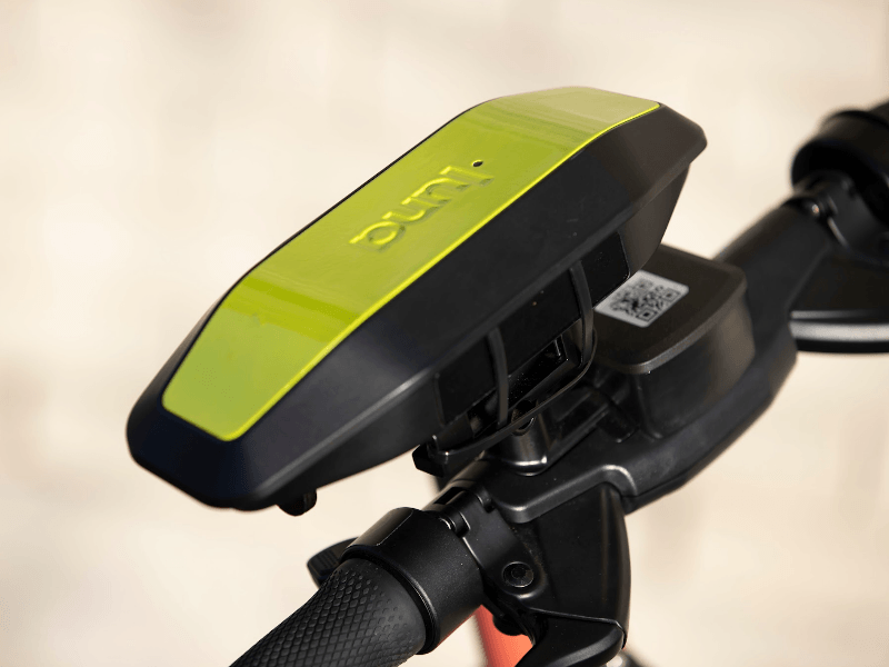 A yellow and black device that says 'Luna' is attached to the handlebars of an e-scooter.
