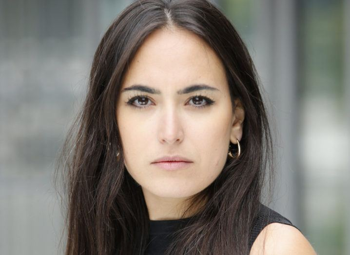 A headshot of Nadine Torbey standing outside a glass building.
