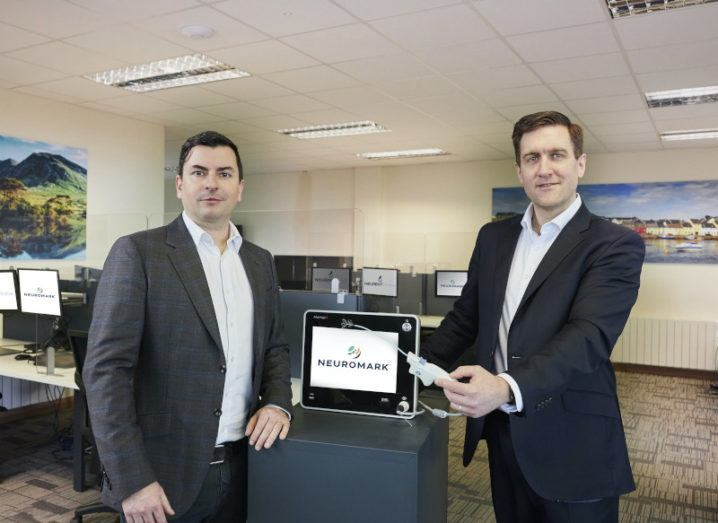 Neurent Medical's founders stand in an office on either side of their medtech device.