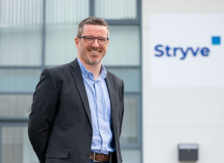 Paul Delahunty is wearing a suit and standing outside an office with the Stryve logo.