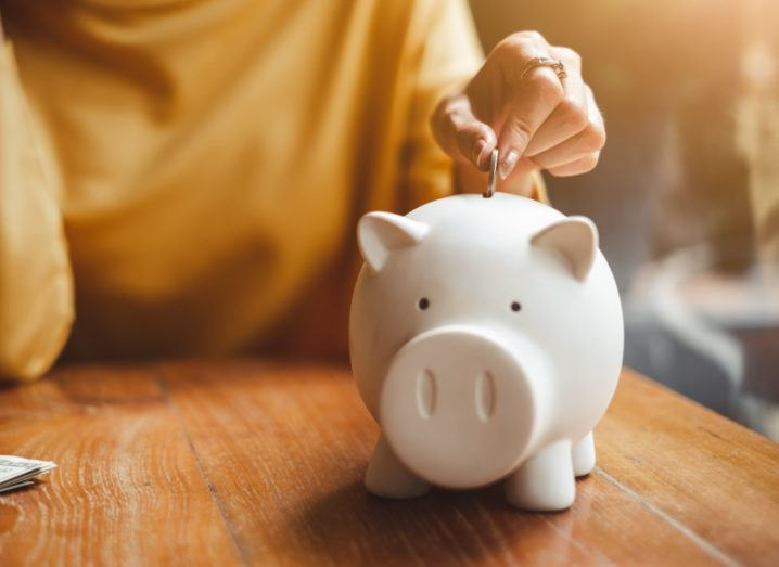 A person in a yellow jumper places a coin in a piggy bank.