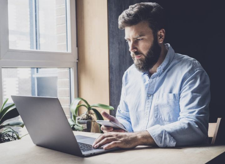 A man remote working on a laptop at a table beside a window with plants on it.