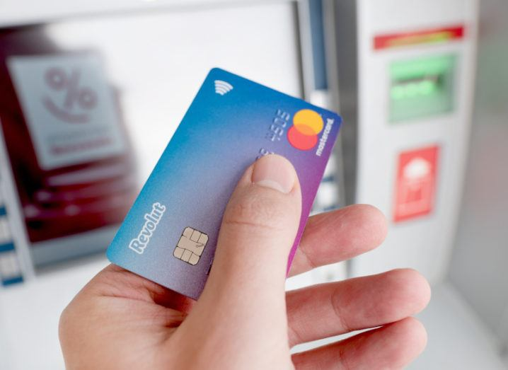 A hand holding a Revolut bank card in front of an ATM.